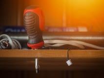 Tournevis sur l'étagère avec d'autres outils photographie stock libre de droits