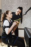 Tourniquet exercises closeup. Trainer assists female athlete to make gymnastic tourniquet exercises, supported with electric muscle stimulation purposed to Royalty Free Stock Photo