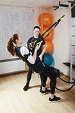 Tourniquet exercises. Couch assisting female athlete to make gymnastic tourniquet exercises, supported with electric muscle stimulation purposed to increase Royalty Free Stock Photos