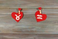 Touro e Aquário sinais do zodíaco e do coração backg de madeira foto de stock royalty free