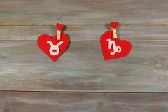 Touro e Capricórnio sinais do zodíaco e do coração Parte traseira de madeira fotos de stock royalty free
