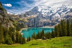 Tourquise stupefacente Oeschinnensee con le cascate, il chalet di legno e le alpi svizzere in Berner Oberland, Svizzera Fotografia Stock