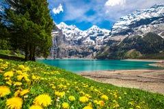 Tourquise stupefacente Oeschinnensee con le cascate, il chalet di legno e le alpi svizzere, Berner Oberland, Svizzera Immagini Stock