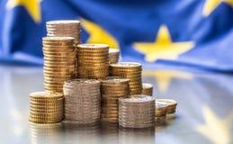 Tours avec d'euro pièces de monnaie et drapeau d'Union européenne à l'arrière-plan images libres de droits