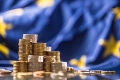 Tours avec d'euro pi?ces de monnaie et drapeau d'Union europ?enne ? l'arri?re-plan photographie stock libre de droits