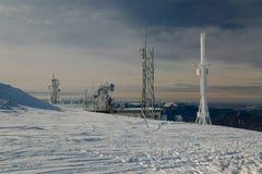 Tours d'émetteur sur une colline en hiver Photos stock