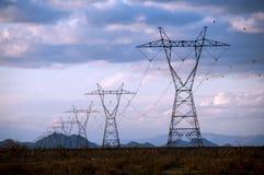 Tours d'Electric Power dans le coucher du soleil Photographie stock