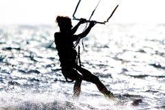 Tours d'un cerf--surfer de jeune femme contre le soleil Photographie stock