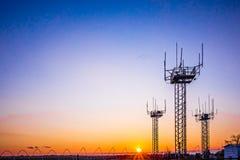 Tours de communication d'aéroport au coucher du soleil Image libre de droits