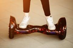 Tours de fille sur le gyroscooter Jambes du ` s d'enfant dans des espadrilles dessus sur mini segway Photographie stock