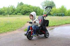 Tours heureux d'enfant sur le vélo dans l'été Photo libre de droits