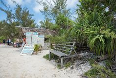 Tours on Mystery Island. MYSTERY ISLAND, VANUATU, PACIFIC ISLANDS: DECEMBER 2,2016: Beach shack, tour signs and people on the sandy shore with tropical flora Royalty Free Stock Photos