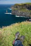 Cliffs of Moher, Ireland, rocky sea shore, legs in hiking shoes Stock Photo