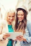 Toursits bonitos das meninas que olham no PC da tabuleta Imagens de Stock