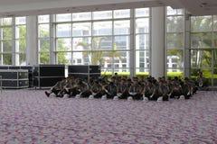 Tous les gardes de sécurité s'asseyant au sol Image stock