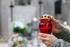 Tous les jour de ` de saints et mains de chrétien avec la lumière de bougie de la mémoire sur le cimetière photos libres de droits