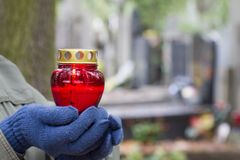 Tous les jour de ` de saints et mains de chrétien avec la lumière de bougie de la mémoire sur le cimetière photographie stock