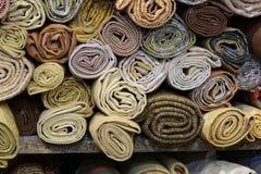 Tous rouleaux de tissu précieux sur l'étagère de la mercerie Image stock