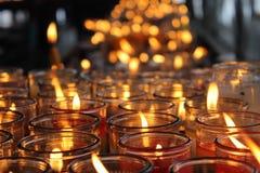 Tousands des bougies jaunes dans une vieille église Image libre de droits