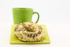 Tout bagel avec du café frais dans la tasse verte Image libre de droits