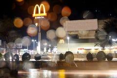Tout en conduisant au logo de mcdonald de nuit par la fenêtre de voiture par le temps pluvieux photographie stock libre de droits