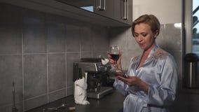 Tout en employant sa femme blonde célibataire de téléphone buvant du vin rouge d'un verre dans une cuisine utilisant la robe bleu banque de vidéos