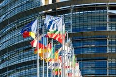 Tout l'Eu marque la zone euro ondulant contre le buildin du Parlement européen Photos stock