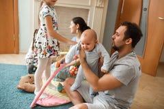 Tout le père de famille, mère, deux filles et peu de fils de bébé passant le temps sur le tapis dans la chambre photos stock