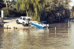 Tout le véhicule de terrain remorquant une remorque avec un bateau sur le dessus dans la rivière Image stock
