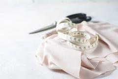 Tout pour la couture Tissu beige, accessoires de couture et ciseaux Photographie stock
