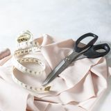 Tout pour la couture Tissu beige, accessoires de couture et ciseaux Image stock