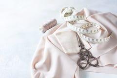 Tout pour la couture Tissu beige, accessoires de couture et ciseaux Photographie stock libre de droits