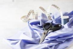 Tout pour la couture Tissu beige, accessoires de couture et ciseaux Photos stock