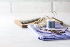 Tout pour la couture Tissu beige, accessoires de couture et ciseaux Photo stock