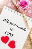 Tout que vous avez besoin est amour sur le journal intime avec le coeur rouge et s'est levé Image stock