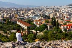 Toutist, das auf einem Felsen über der Akropolise macht ein Foto von sitzt stockfotografie