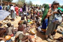 Afrikanen marknadsför och turisten Arkivfoto