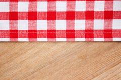 Tovaglia Checkered sulla tabella di legno fotografia stock
