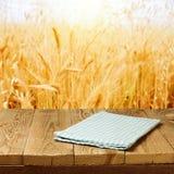 Tovaglia controllata sulla tavola di legno della piattaforma sopra il fondo del giacimento di grano immagine stock