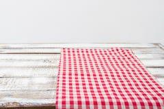 Tovaglia a quadretti rossa su un tavolo da cucina di legno, spazio della copia immagini stock libere da diritti
