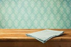 Tovaglia sulla tavola di legno sopra la retro carta da parati fotografia stock