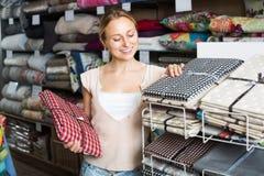 Tovaglie d'acquisto femminili allegre in deposito domestico immagine stock libera da diritti