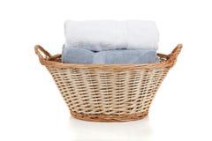 Tovaglioli bianchi e blu in un cestino di lavanderia su bianco Immagini Stock