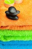 Tovaglioli di bagno Multi-colored e pietre nere della stazione termale Fotografia Stock
