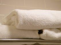 Tovaglioli piegati della peluche in una stanza da bagno Immagine Stock