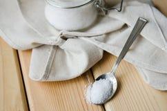 Tovagliolo bianco del sale del mar Bianco in un barattolo su un cucchiaio del ferro Fotografie Stock Libere da Diritti