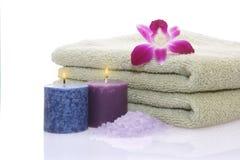 Tovagliolo, candele, orchidea e sale di bagno verdi Fotografie Stock Libere da Diritti