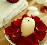tovagliolo di rosa delle pietre dei petali della candela Fotografia Stock