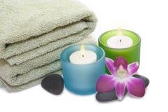 Tovagliolo, orchidea, candele e ciottoli verdi Fotografia Stock Libera da Diritti