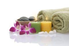 Tovagliolo, orchidea, candele e ciottoli verdi su priorità bassa bianca Fotografie Stock
